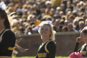Sammie Davidson, dressed in a black cheerleading uniform and standing in front of the Memorial Stadium stands, smiles and stares off-camera.