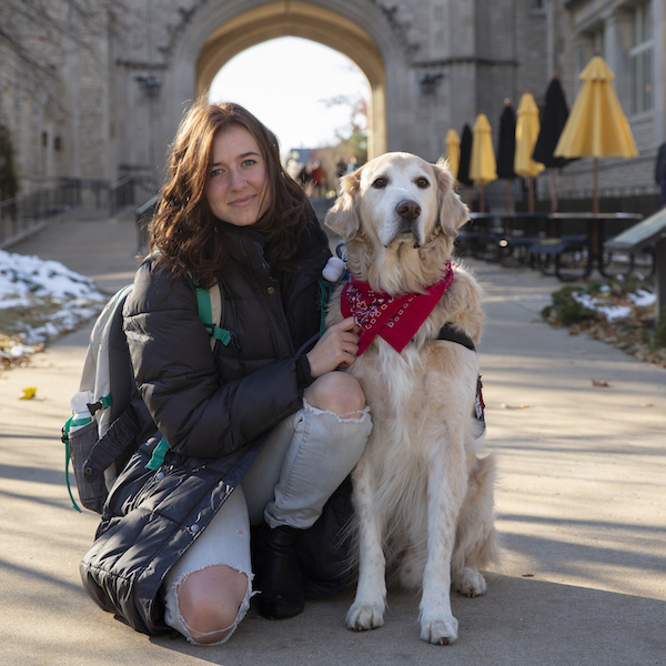 Sophie Endacott kneels next to her service dog, Hudson, in front of the Memorial Union tower.