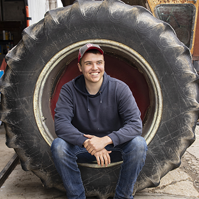 Gavin sits in a tractor tire smiling off-camera