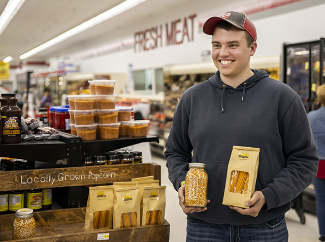 Gavin stands in a grocery store next to a display with Spoor Farms popcorn and holding the product