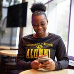 A young alumna using her phone in the student center.