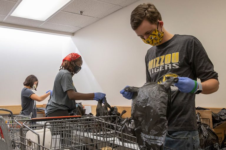 Peter Mallon, a chemistry major from Liberty, MO, packages food items while volunteering at Tiger Pantry.