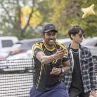 Ashen Samaranayake (center), a PhD student in Chemistry, plays cornhole at the Dean of Students tailgate on the Southwest Village lawn Oct. 09, 2021
